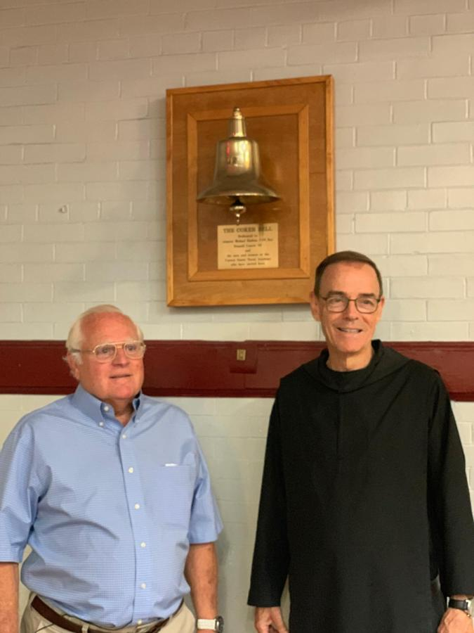 Fr. Edwin and Mr. Coker pose by the Coker Bell named after the war hero.