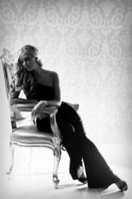 Model in long black formal dress sat on a chair