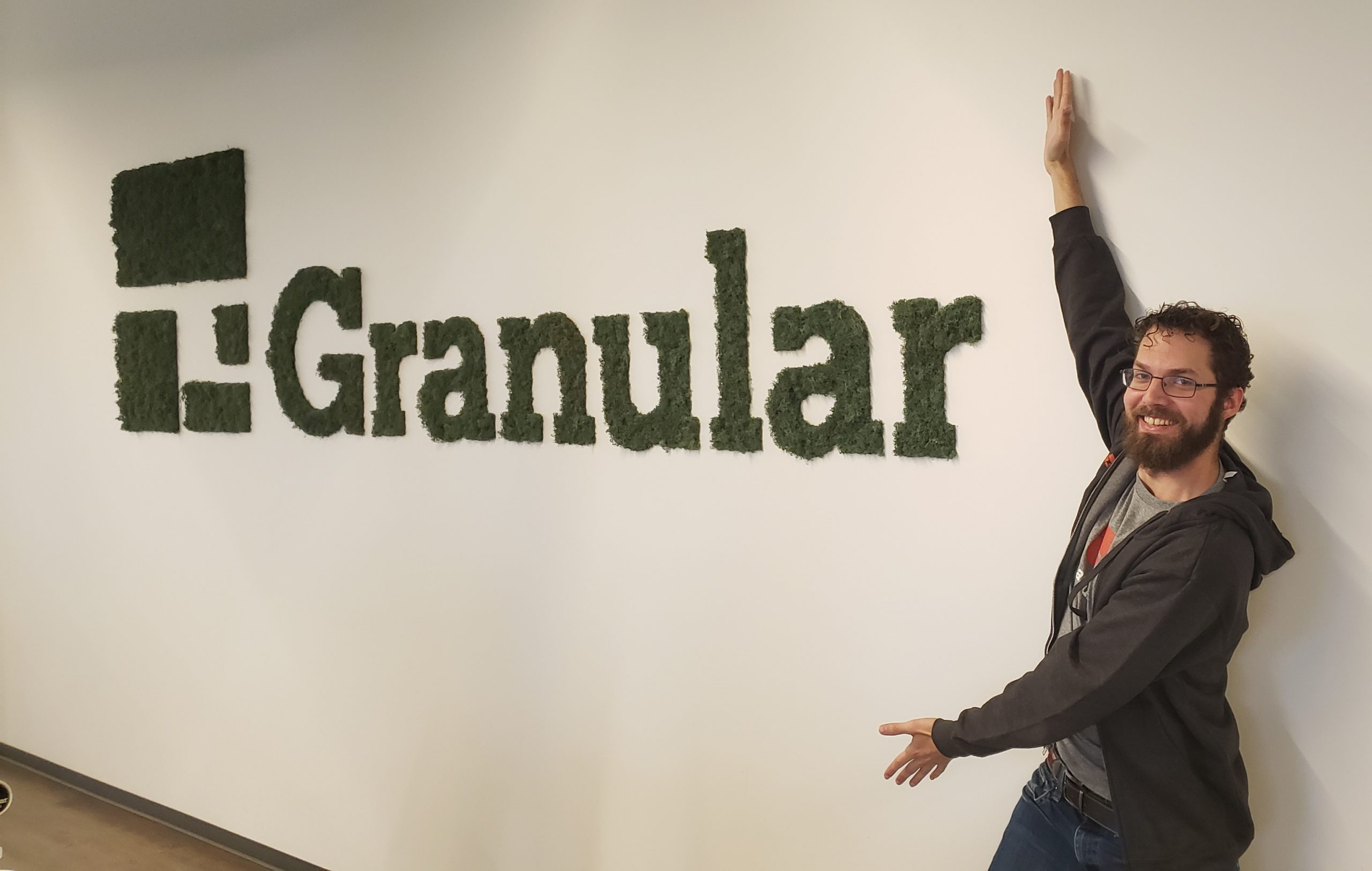 At the Granular office, my arms outstretched pointing at the logo