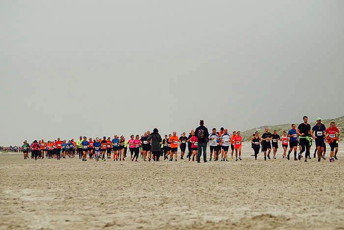 Lopers van de halve marathon op het strand tijdens de Berenloop van 2015