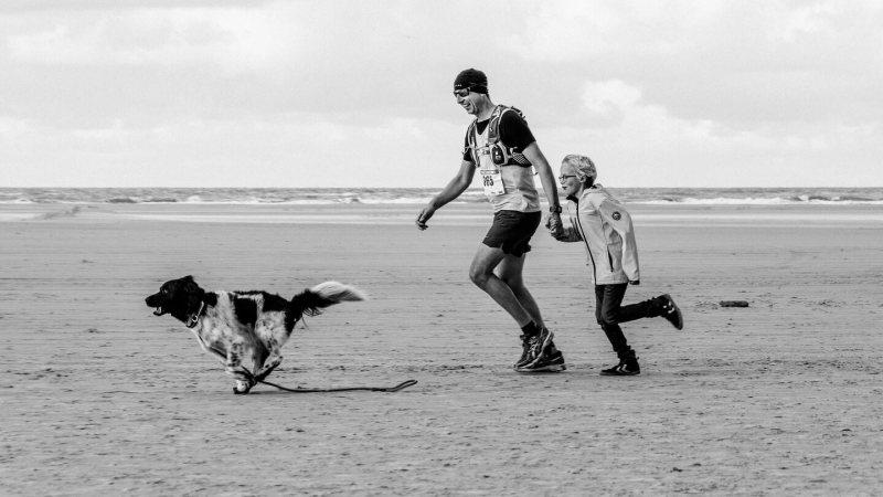 Berenloper met hond en kind op he strand tijdens de Berenloop 2017.