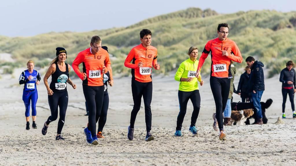 Drie lopers van de Special Forces Hardlopers op het strand tijdens de halve marathon van de Berenloop 2018.