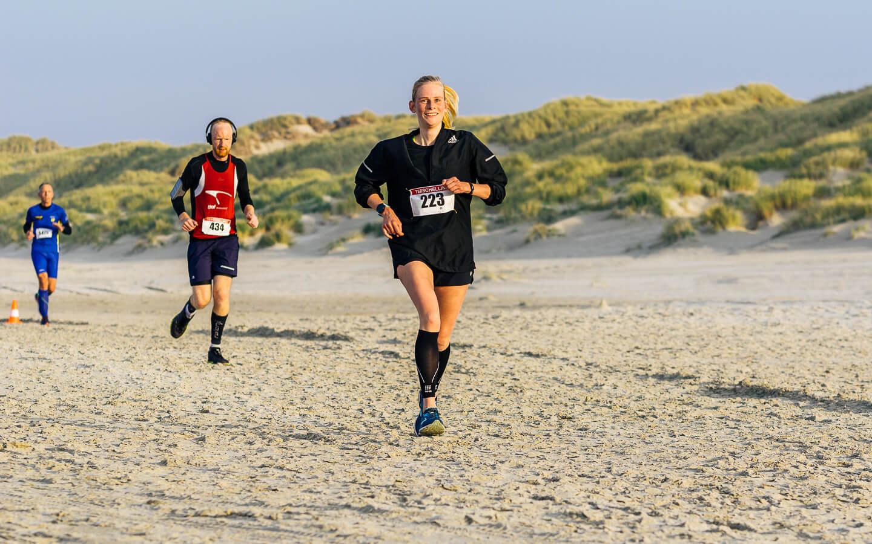Berenloopster op het strand tijdens de hele marathon van de Berenloop 2018.
