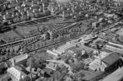 Oversiktsbildet fra 1955 viser Fagerheim Fabrikker AS til nederst til venstre, den store låven like ovenfor ved gårdsveien, og våningshuset innimellom trærne ved siden av. Fotograf: Widerøes Flyveselskap. Billedsamlingene UBB.