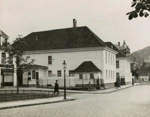 """Det Gamle Teater (""""komediehuset på Engen"""") sett fra Teatergaten. Fredet i 1927, men sterkt skadet ved bombeangrep i 1944, og senere revet. Fotograf: Ukjent. Arkivet etter Kommunalavdeling fritid, kultur og kirke, Bergen Byarkiv."""