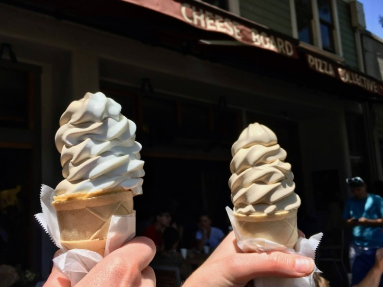 Two hands hold up cones of soft serve ice cream in front of the Cheese Board in Berkeley.