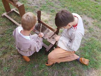 Vergrößerung: Kinder verarbeiten Flachs im germanischen Gehöft