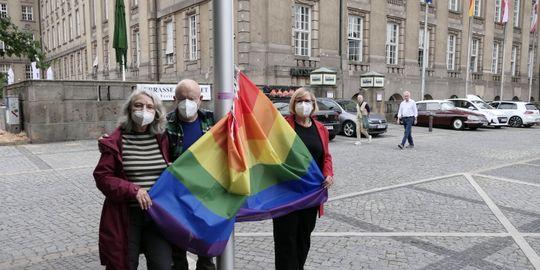 Drei Menschen in Masken halten eine Regenbogenfahne, die an einem Fahnenmast hängt.