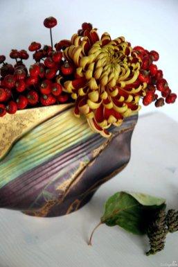 Chrysantheme und Hagebutten in einer länglichen Vase