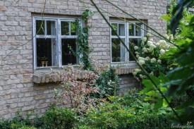 Gartenhaus aus recycelten Steinen und Fenstern