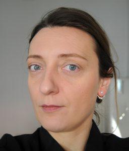 Eine Frau mit blauen Augen und hellbraunem Haar, die zurückgebunden ist, starrt direkt in die Kamera und lächelt leicht.