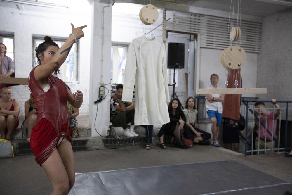 Eine Performerin steht links im Vordergrund. Rechts hängen zwei Kleider und Holzkonstruktionen von der Decke. Im Hintergrund sitzt und steht das Publikum.