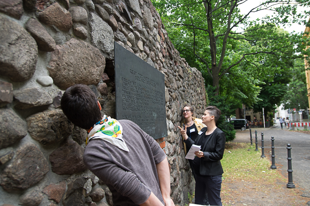 Three persons outside looking from different sides at and behind a metal board with writing attached to the wall