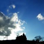 church on hill with sun