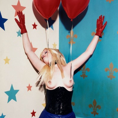 Woman in corset with red balloons attached to her pierced nipples.