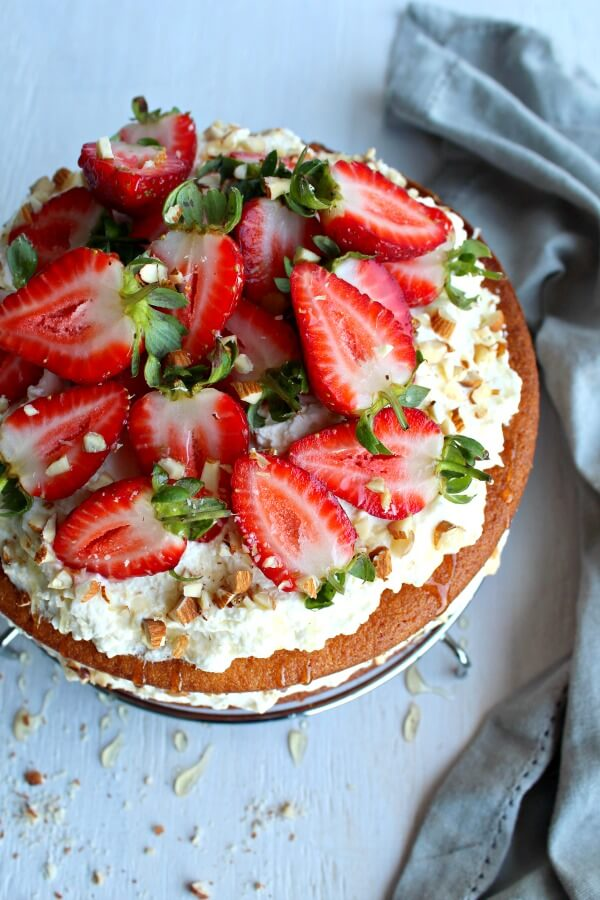 Zesty Orange Honey Layer Cake. The moistest, most tasty orange sponge cake with whipped cream & chopped almond layers & fresh strawberries on top. AMAZING! | berrysweetlife.com