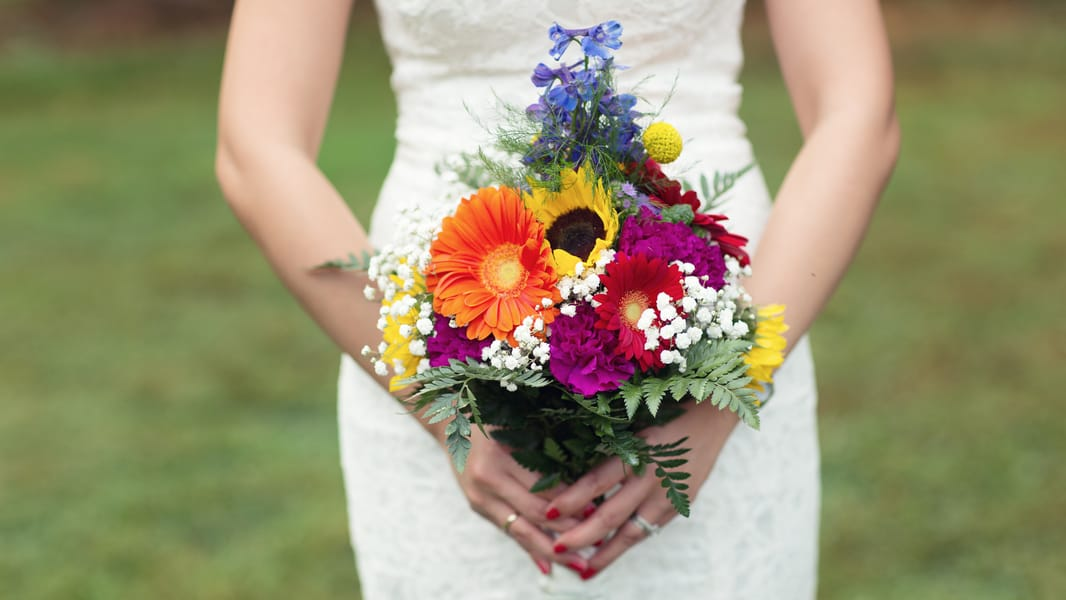 colourful wedding bouquet with sunflowers and yellow and orange colour rainbow colour scheme