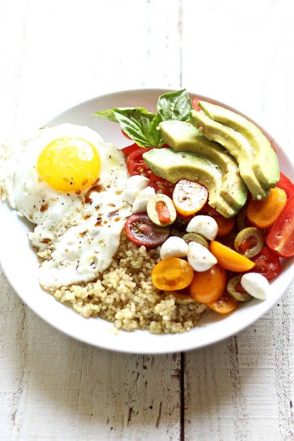 Try a healthy and delicious quinoa breakfast bowl packed with a crispy egg, avocado, cherry tomatoes, olives, and mozzarella
