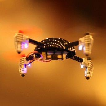 Drone quadricottero in volo su sfondo arancio e nero