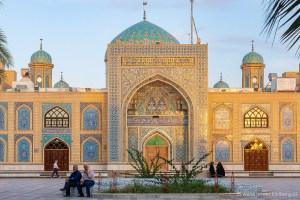Twee mannen zitten voor de betegelde moskee van Tabas in Iran in het avondlicht