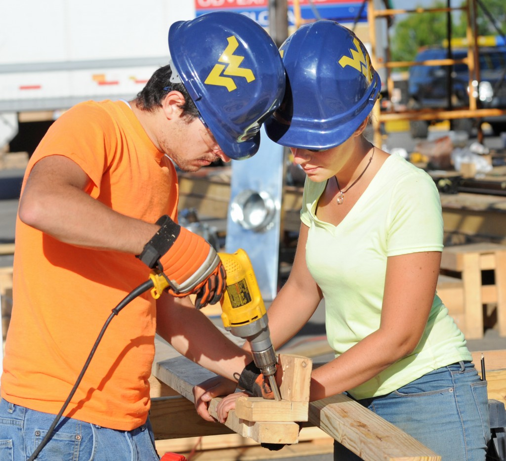 Damiano Paparelli (left) and Tiziana Costanzo of Team West Virginia/Rome work together drilling holes for deck panels on Day 5 of the U.S. Department of Energy Solar Decathlon at the Orange County Great Park, Irvine, California Friday, Oct. 2, 2015. (Credit: Thomas Kelsey/U.S. Department of Energy Solar Decathlon)