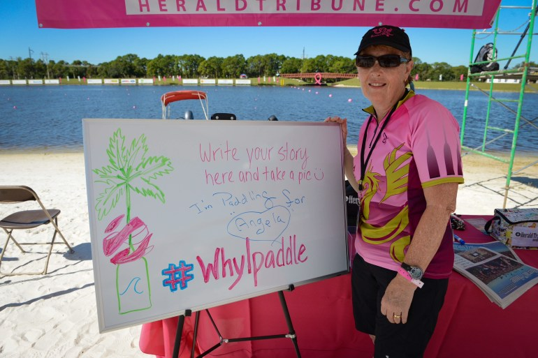 Debbie Bachman from Bouyant Buddies shows why she paddles on a whiteboard at the Sarasota Herald-Tribune tent Saturday, October 25 during the 2014 Dragon Boat Festival at Nathan Benderson Park. (October 25, 2014) (Herald-Tribune staff photo by Rachel S. O'Hara)
