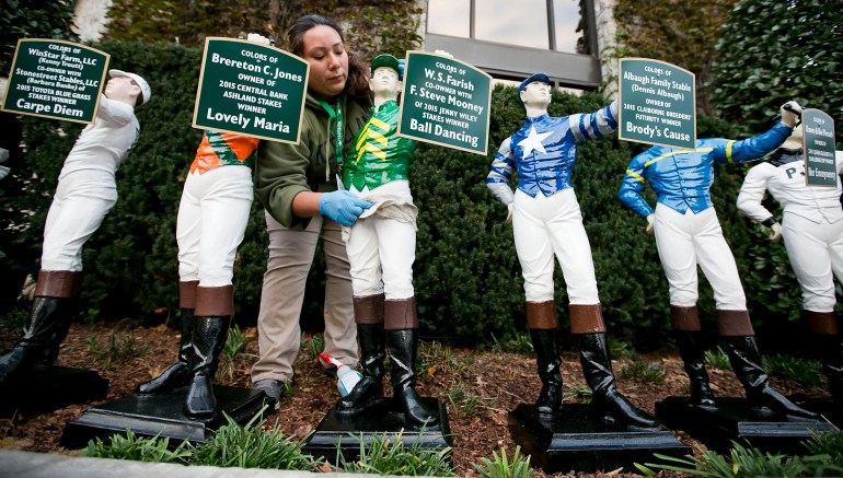 Blanca Martinez cleans the lawn jockeys at Keeneland Race Track Friday afternoon October 30, 2015 in Lexington, KY during the first day of the 2015 Breeders' Cup. In the two days of racing, about 60 horses have Marion County ties. (Doug Engle/Ocala Star-Banner)2015.