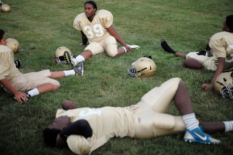 Shaniqua Scott, center, stretches with some of her teammates before the start of the game.