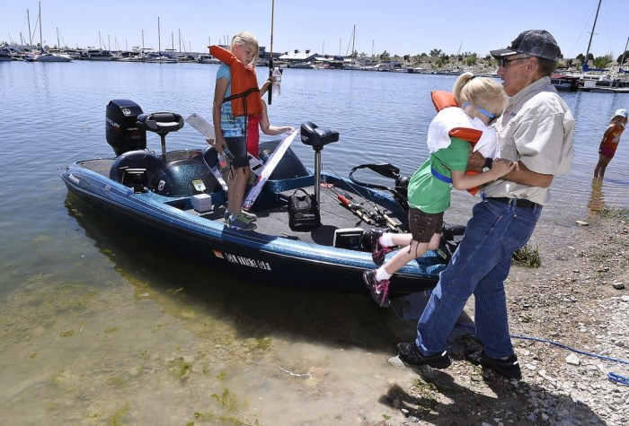 Ken Necessary (right) a member of the Pikes Peak Bass Masters, helps unload Gabrielle Meinders, 6, and her sister Makenzie Meinders, 10, along with mom Tessa (in back)  after a morning of fishing at Lake Pueblo. The girls were taking part in the Fort Carson Military Kids Fishing Day, in Pueblo Colo. on June, 14, 2014. (John Jaques,The Pueblo Chieftain)