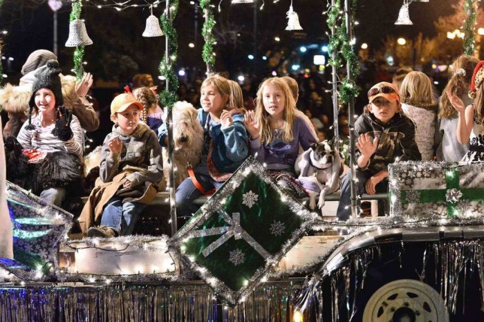 Children riding on the 4H Pups and Hounds float wave to crowd as the ride in the 2014 Parade of Lights heading down Union Avenue in Pueblo Colo. on Nov. 29, 2014. (John Jaques,The Pueblo Cheftain)