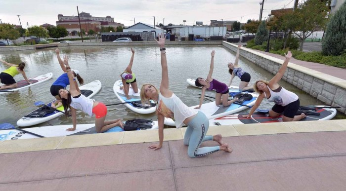 Lindsay Smith (center) conducts a paddle board yoga class in Gateway Park on the Historic Arkansas Riverwalk in Pueblo Colo. on July 13, 2015. (John Jaques,The Pueblo Chieftain)