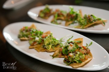 Corn tortillas topped with guacamole, salsa, pickled jalapenos, and pumpkin seeds