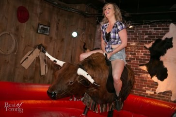 A Spurlesque girl riding the mechanical bull
