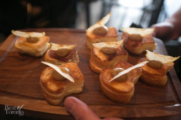 Grilled cheese bites topped with apple butter and a chip for appetizers