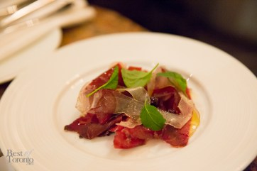 """house-cured, air-dried Bison """"Pemmican"""" Bresaola is thinly shaved and paired with house-made lardo, lightly dressed with Chef's wild blueberry juniper vinaigrette"""