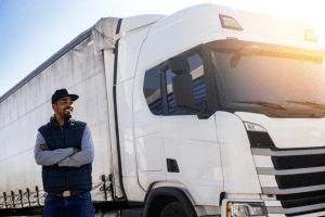 Black truck driver standing next to truck. Diversity in the trucking industry is still a work in progress