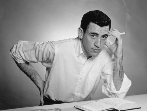 "NEW YORK - NOVEMBER 20, 1952: Author JD Salinger poses for a portrait as he reads from his classic American novel ""The Catcher in the Rye"" on November 20, 1952 in the Brooklyn borough of New York City. Salinger died on January 27, 2010. (Photo by Antony Di Gesu/San Diego Historical Society/Hulton Archive Collection/Getty Images)"
