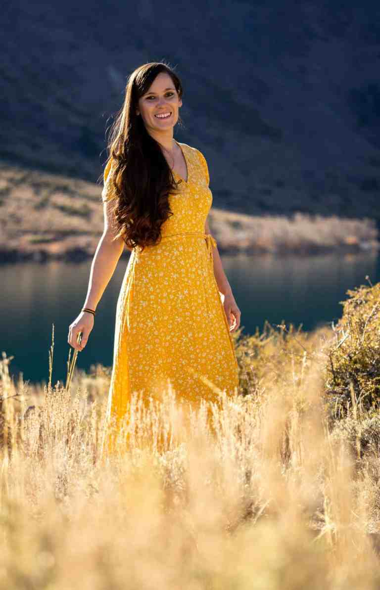 Toni Jacalone poses in a meadow while wearing a long yellow dress