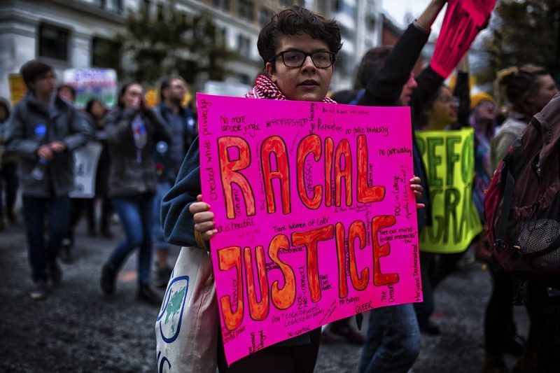 woman holding a sign that says racial justice