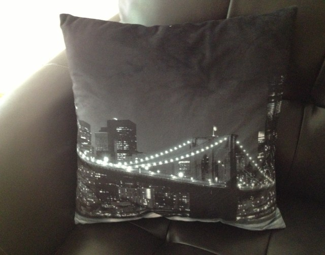 Black pillow with lighted bridge and city