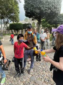 Beth Jones giving out orange drinks to indigenous in Parque Central, Antigua