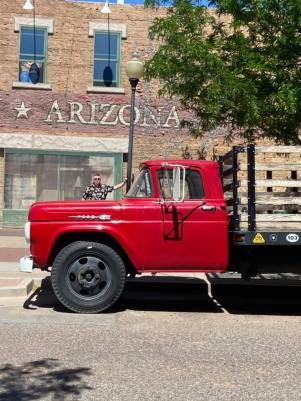 red Ford flatbed truck on corner in Winslow, AZ