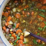a large pot of beef vegetable soup with carrots, potatoes, green beans, peas, and corn