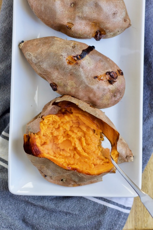 a tray of baked sweet potatoes with one cut open to reveal tender orange goodness