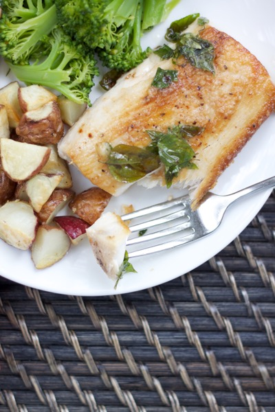 a flaky bite of fish on a plate with roasted potatoes and broccoli
