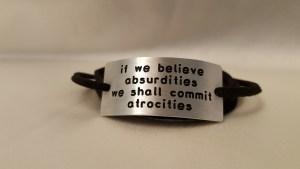 "bracelet tht reads, ""if we believe absurdities, we shall commit atrocities"""