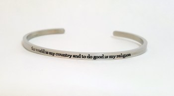 silver cuff bracelet with text the world is my country and to do good is my religion