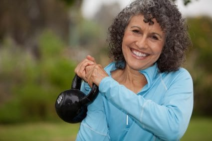 A vibrant woman in her 60s holds a kettlebell.