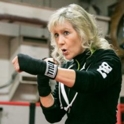 Photo of blonde woman wearing athletic wear, instructing boxing moves. Kimberly Berg Rebel Fit Club