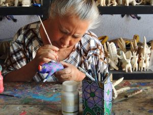 older woman painting artisan